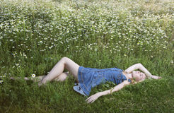 The beautiful happy young woman lies in the field of chamomiles Stock Images