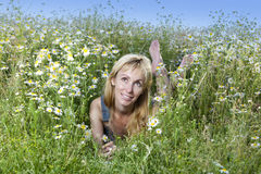 The beautiful happy young woman lies in the field of chamomiles Royalty Free Stock Images