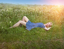 Beautiful happy young woman lies in the field of chamomiles Stock Images