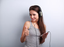 Beautiful happy young woman listen the music holding the phone a Stock Images