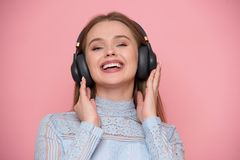 Beautiful happy young woman listen music and using mobile application isolated on white. Royalty Free Stock Photography