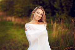 Beautiful happy young woman with long hair standing in the eveni. Ng sun, turning to the white blanket and smiling fun. Romantic date in nature Stock Photography
