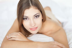 Beautiful happy young woman lying on bed Stock Image