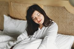 Beautiful happy young woman lying in bed in the morning in hotel room or home bedroom. Stylish brunette girl in white relaxing on stock photography