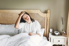 Beautiful happy young woman lying on bed in the morning in hotel room or home bedroom. Stylish brunette girl in white relaxing on royalty free stock photo
