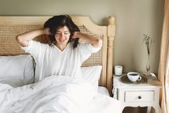 Beautiful happy young woman lying on bed in the morning in hotel room or home bedroom. Stylish brunette girl in white relaxing on royalty free stock photography