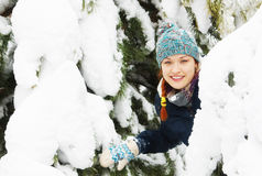 Beautiful happy young woman peeks out from behind snowy pine tree Stock Photo