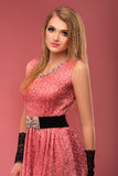 Beautiful happy young woman in pink dress on pink background royalty free stock photo