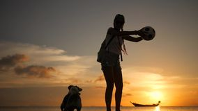 Beautiful happy young woman playing with jack russell dog at beach during amazing sunset. Koh Phangan, Thailand. HD stock footage