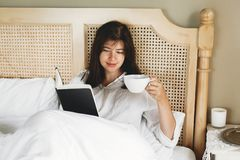 Beautiful happy young woman reading book and drinking coffee in bed in hotel room or home bedroom. Stylish brunette girl in white royalty free stock photo