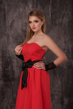 Beautiful happy young woman in red dress on grey background stock photo