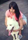 Beautiful happy young woman in shorts with white husky dog Stock Photos