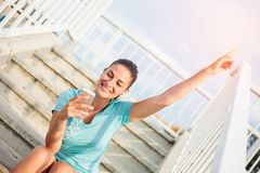 Beautiful happy young woman sitting on a steps and relaxing after a hard workout royalty free stock images