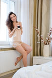 Beautiful happy young woman sitting on windowsill and drinking coffee Royalty Free Stock Photos