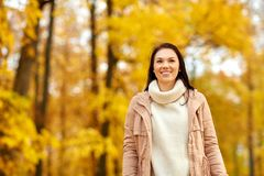 Beautiful happy young woman smiling in autumn park. Season, emotions, facial expression and people concept - happy young woman smiling in autumn park stock photos