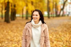 Beautiful happy young woman smiling in autumn park. Season, emotions, facial expression and people concept - happy young woman smiling in autumn park stock image