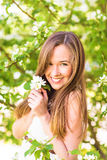 Beautiful happy young woman in the spring garden among apple blossom, soft focus Royalty Free Stock Photo
