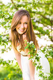Beautiful happy young woman in the spring garden among apple blossom, soft focus Royalty Free Stock Images