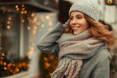 Beautiful happy young woman with a sweet smile in fashionable. Vintage knitwear with a knitted cap and scarf walking outdoors on holidays near yellow lights stock photography
