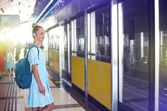 Beautiful happy young woman traveling in metro. Waiting for train royalty free stock photos