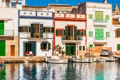 Idyllic fishing village harbour of Porto Colom on Mallorca island, Spain. Beautiful harbor with colorful houses of Porto Colom at the coast of Mallorca, Spain Royalty Free Stock Images