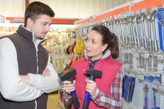 Beautiful hardwarestore saleswoman helping customer. Attractive stock photography