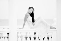 The beautiful harmonous girl with long hair on seacoast. In a long light dress Royalty Free Stock Images