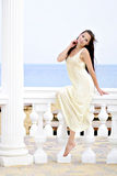 The beautiful harmonous girl with long hair on seacoast. In a long light dress Stock Images
