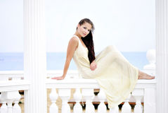 The beautiful harmonous girl on seacoast. The beautiful harmonous girl with long hair on seacoast in a long light dress Stock Photography