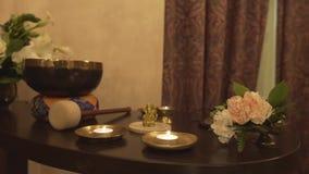 Beautiful hatha yoga meditation buddhism religion ayurveda items scented candle bronze tibetan singing bowl on table stock video footage