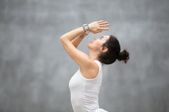 Beautiful Hatha Yoga. Side view portrait of beautiful young woman wearing sport watch for heart rate and calorie burn control working out against grey wall Stock Image