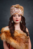 Beautiful haughty queen in royal dress. Sexy girl in royal hat and fur coat. Luxury woman in traditional dress Stock Images