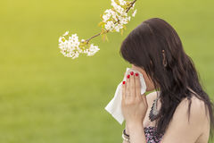 Beautiful hayfever girl wiping her nose in spring nature. The beautiful young woman is pained by her allergy every year. She holds a tissue in her hands Royalty Free Stock Images