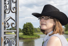 Beautiful head shot of a woman wearing glasses and a black cowboy hat. Stock Photos