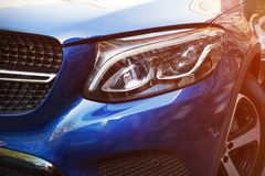 Beautiful headlight of blue car by close-up in a sunny day. Kind with to the side royalty free stock images