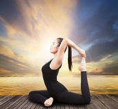 Beautiful health care asian woman posting yoga at wood terrace Royalty Free Stock Image