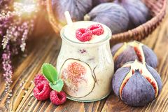 Beautiful healthy appetizer figs fruit smoothie milk shake in glass jar decorated fresh figs pink raspberries  top view. Natural d. Etox Liquid ice cream. Yogurt Royalty Free Stock Image
