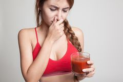 Beautiful healthy Asian girl hate  tomato juice. Royalty Free Stock Images