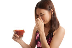 Beautiful healthy Asian girl hate  tomato juice. Royalty Free Stock Photo
