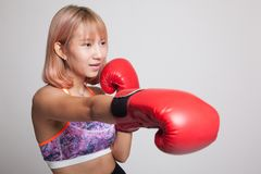 Beautiful healthy Asian girl with red boxing glove. Stock Photo