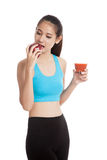 Beautiful healthy Asian girl with tomato juice and apple Royalty Free Stock Photos