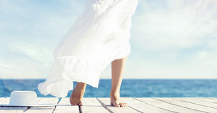 Beautiful and healthy feet of a young girl in white dress on a w. Ooden pier. Sea and sky background. Vacation, resort and traveling concept Stock Images
