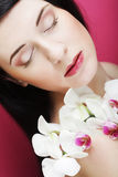 Beautiful healthy woman with orchid flower. Royalty Free Stock Photos