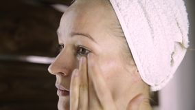 Beautiful healthy woman in a towel putting moisturizing cream on face. Skin care and home Spa stock video