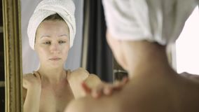 Beautiful healthy woman in a towel putting moisturizing cream on face. Skin care and home Spa stock video footage