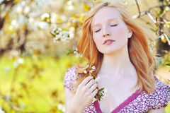 Beautiful healthy young girl in blooming tree. Eyes closed Royalty Free Stock Image