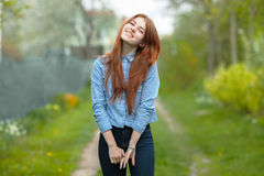 Beautiful healthy young redhead woman having fun on the green grass of country road Royalty Free Stock Photo