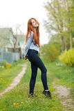 Beautiful healthy young redhead woman having fun on the green grass of country road Royalty Free Stock Photos