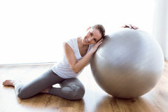 Beautiful healthy young woman doing exercise with ball at home. Stock Image