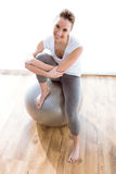 Beautiful healthy young woman doing exercise with ball at home. Royalty Free Stock Images